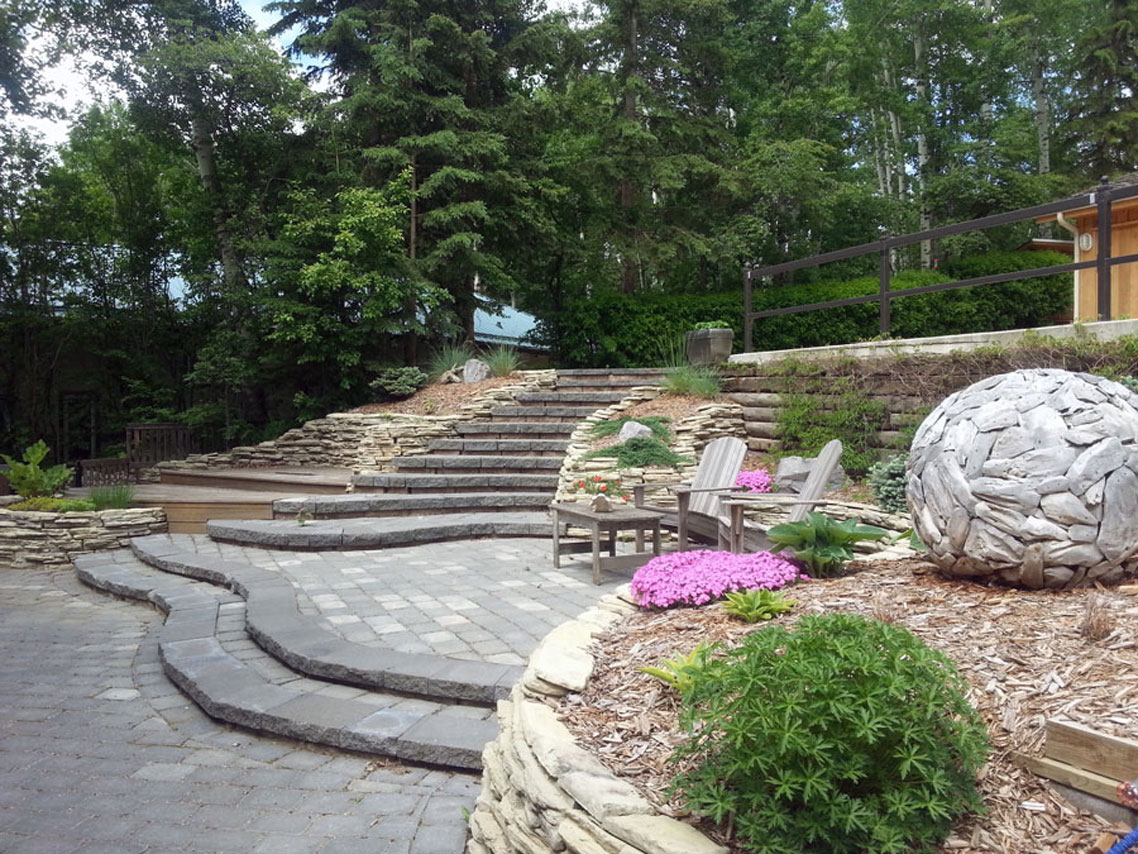 Stone Stairs And A Patio Surrounded By Rock Walls Welcomes You Into This  Garden. A