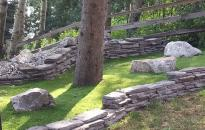 Artificial Turf replaces the poorly growing grass under this tree. Rock wall and boulders add character to this corner of the yard.