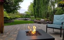 A patio to enjoy a fire while looking out into the garden of shrubs, perennials, rock walls and a waterfall