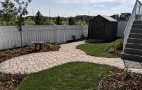 Paving stone sidewalk leads from the deck to the patio and steps down to the park gate and shed