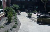 A court yard in a seniors complex with a rotation of blooming perennials and shrubs. A garden box provides a space for fresh vegetables to be grown.