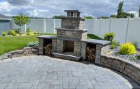 Outdoor fireplace emerging from the rock wall and landscape makes this patio a cozy place to be