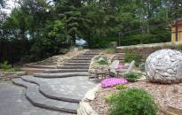 Stone stairs and a patio surrounded by rock walls welcomes you into this garden.  A outdoor sculpture surrounded by perennials is a highlight in this yard.