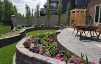 Tiered yard with patio and rock walls made this once sloped yard into a beautiful garden